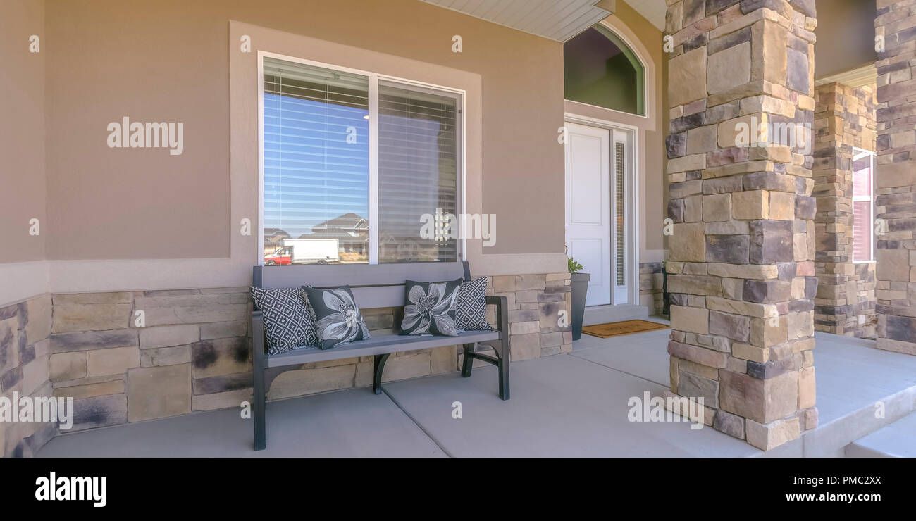 Patio Of A House With A Bench And Pillows In Utah. Grey Bench On The Patio  Of A House With Large Front Window And White Door. Throw Pillows Are Placed