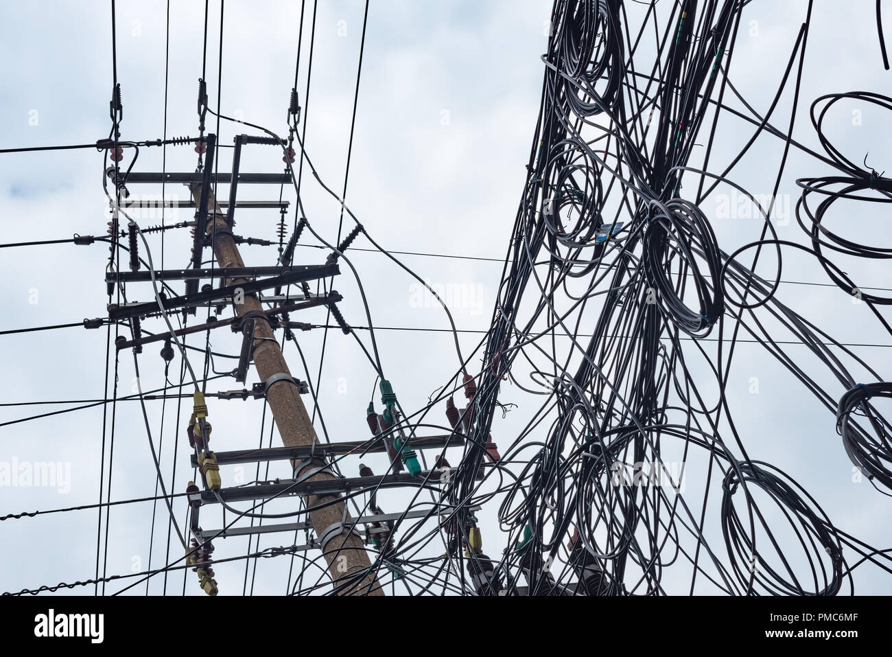 Telephone pole and chaotic mess of wires against sky in China - Stock Image