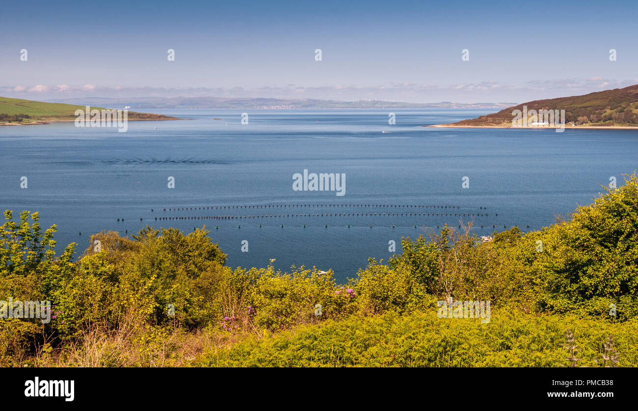 Blue wanter and blue sky fill the view of Lamlash Bay, Holy Island, the Firth of Clyde and the coast of North Ayrshire on Scotland's Isle of Arran. - Stock Image
