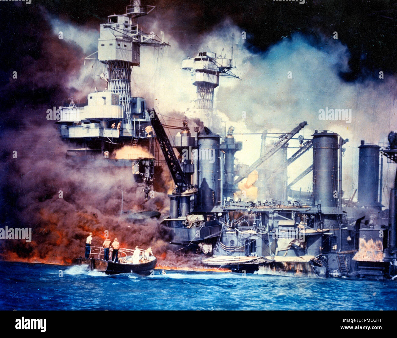 Sailors in a motor launch rescue a survivor from the water alongside the sunken USS West Virginia (BB-48) during or shortly after the Japanese air raid on Pearl Harbor. USS Tennessee (BB-43) is inboard of the sunken battleship.  This is a color-tinted version Photo  It is not an actual color photograph. - Stock Image