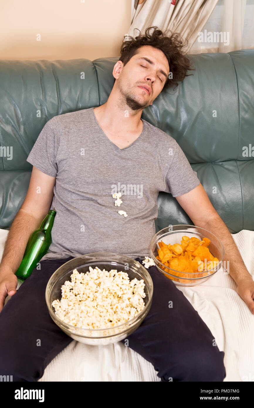 A man sleeping on a couch in a mess of junk food - Stock Image