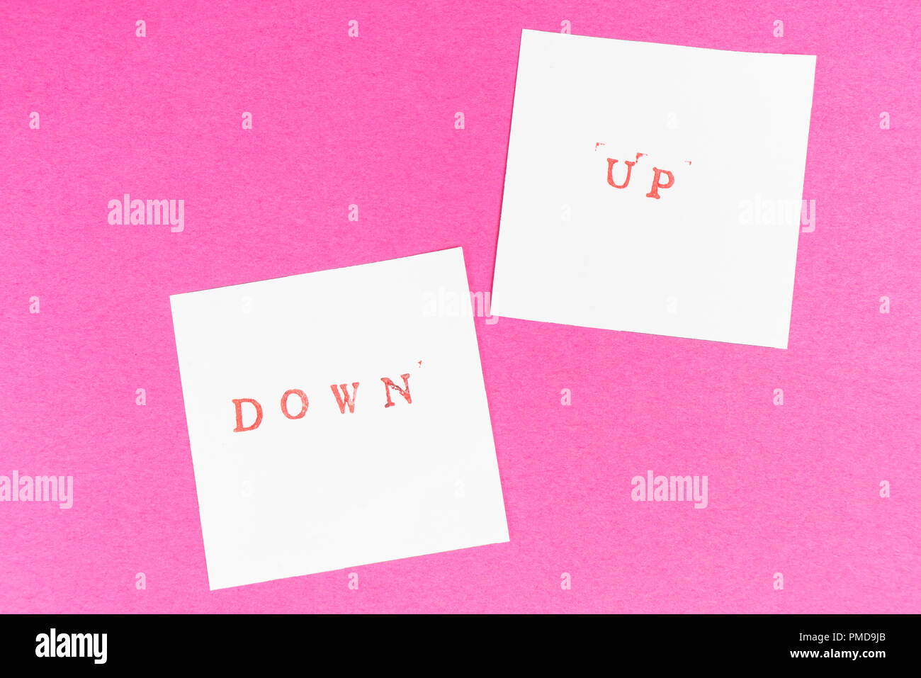 the contrast between the up and down words printed on two sheets of paper - Stock Image