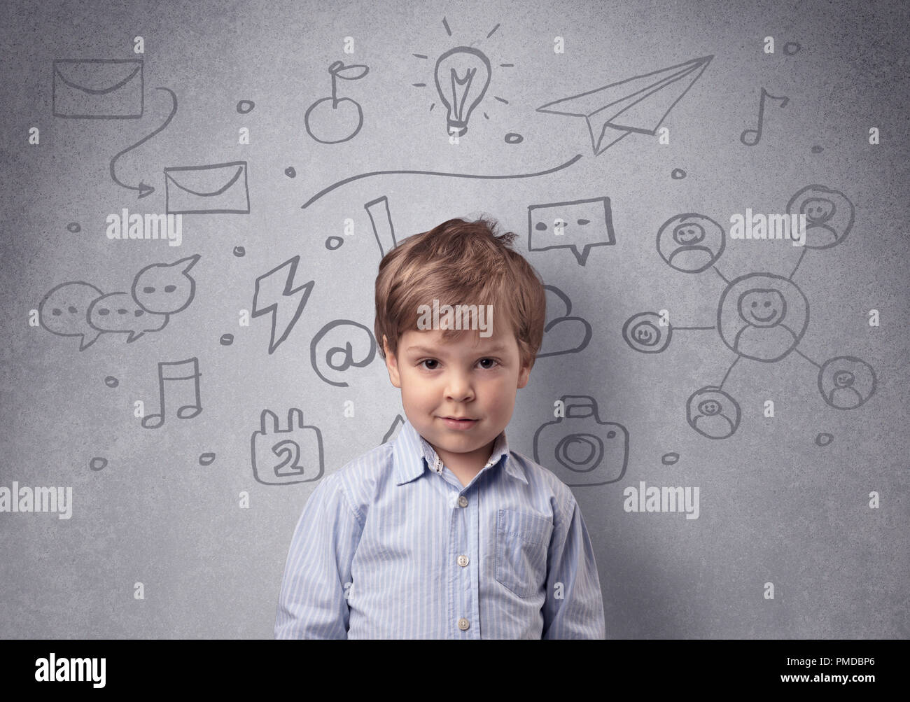 Smart little junior in front of a drawn up grey wall with childlike concept - Stock Image