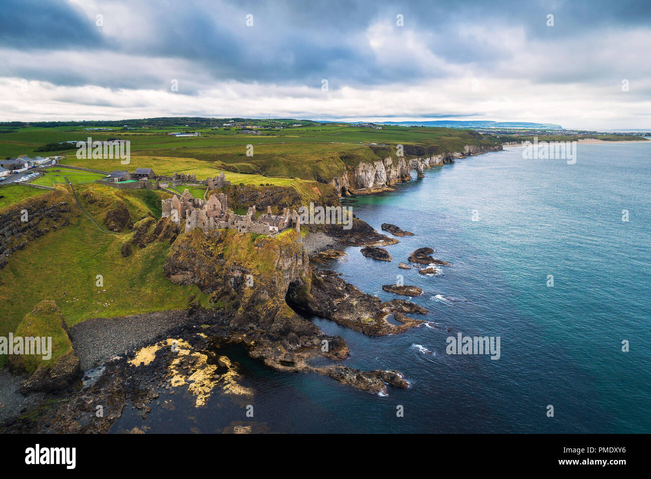 Aerial view of the medieval Dunluce Castle ruins and surrounding cliffs in Ireland - Stock Image