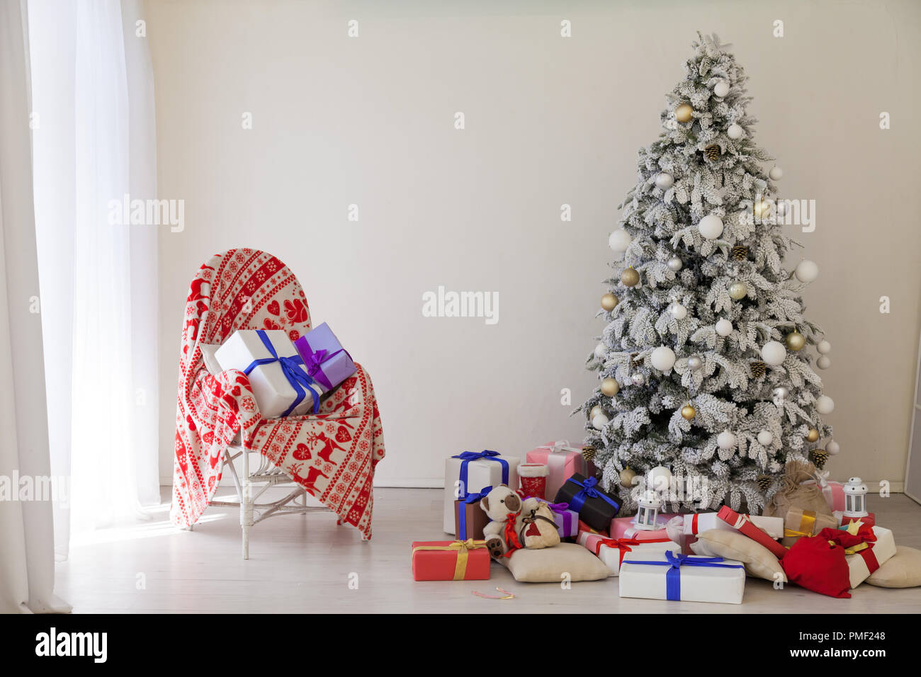 apartment decor for the new year Christmas tree and gifts - Stock Image