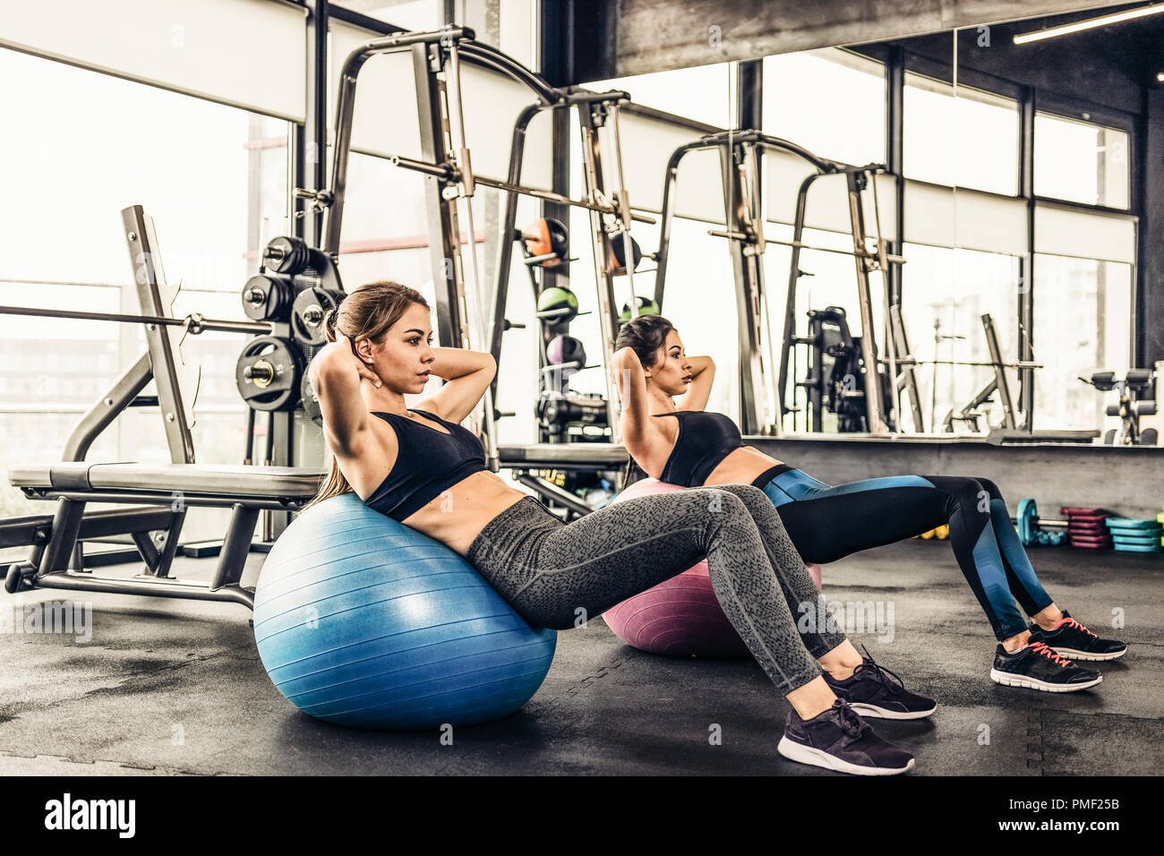 Two cute girls doing heavy athletic workout in the gym doing exercises for abdominal muscles - Stock Image
