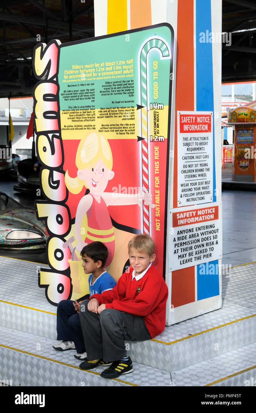 Two young boys sitting under a height restrictions board for a dodgems ride at the funfair - Stock Image