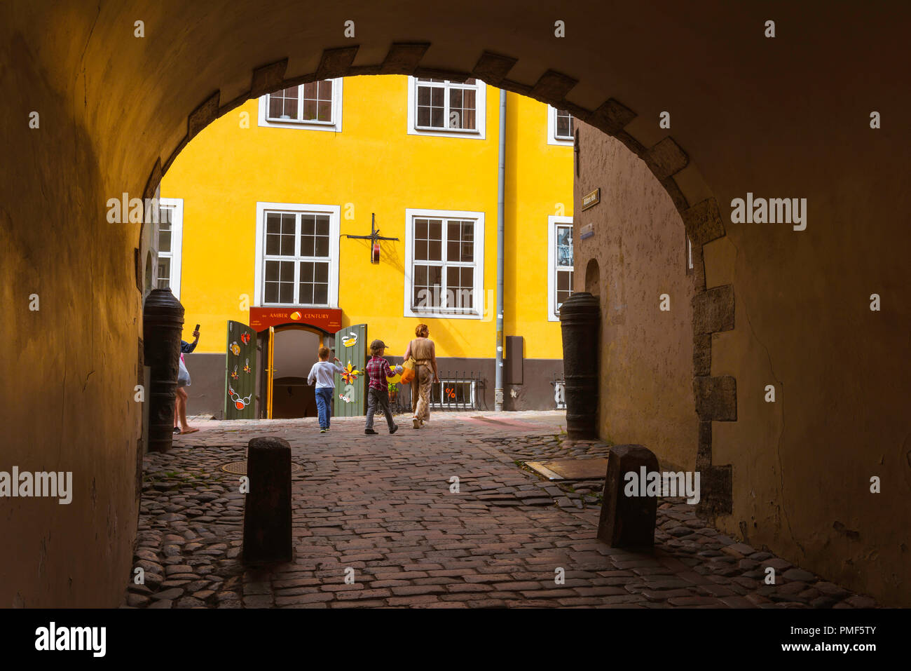 Swedish Gate Riga, view through the Swedish Gate to the colorful row of yellow buildings known as Jacob's Barracks in Tornu Iela in medieval Old Riga. - Stock Image