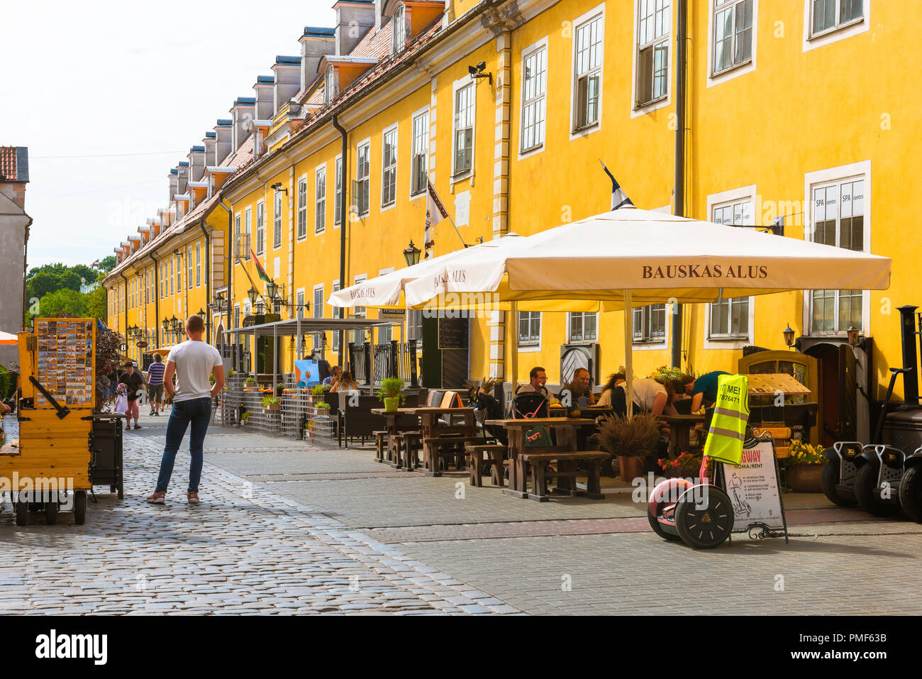 View of people at terrace cafe tables alongside Jacob's Barracks in Tornu Iela, a historic street in the medieval center of Old Riga, Latvia. - Stock Image