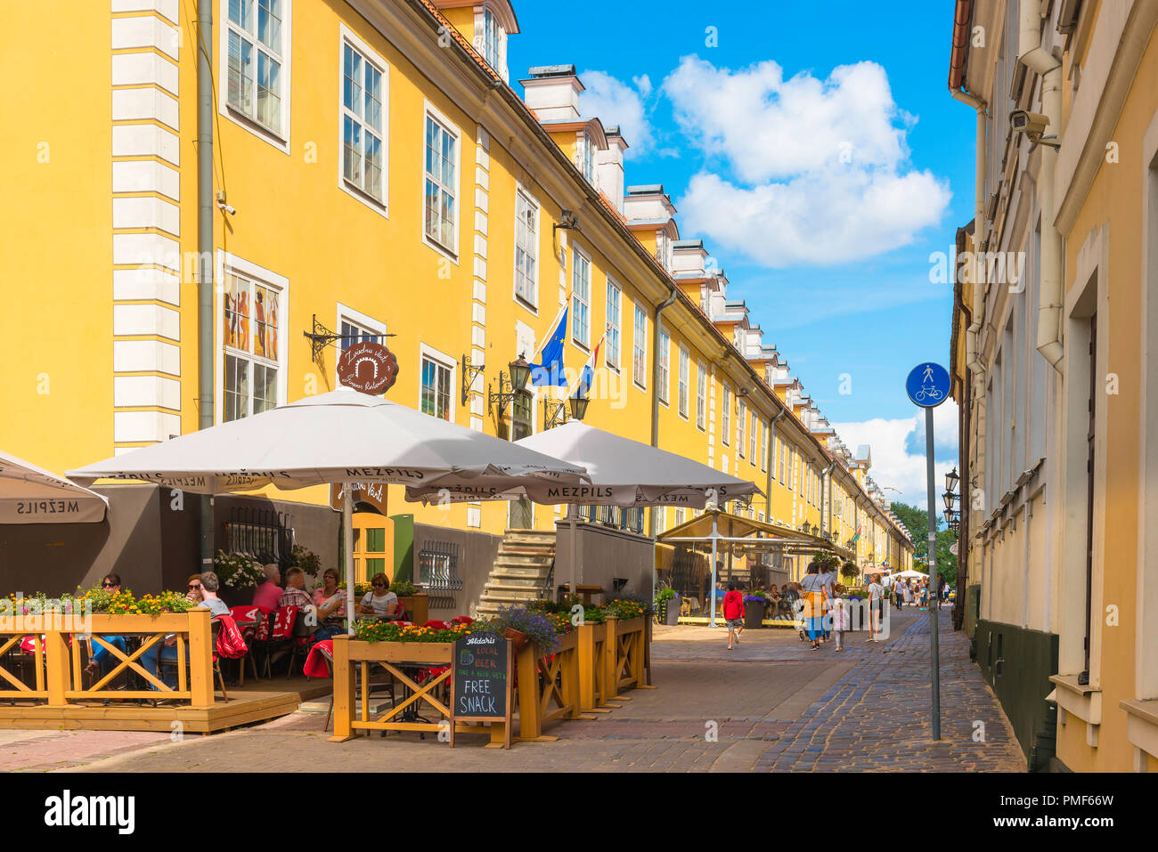 Riga Old Town, view of a cafe restaurant beside the colorful Jacobs Barracks building in Torna Iela in the historic Old Town quarter of Riga, Latvia. - Stock Image