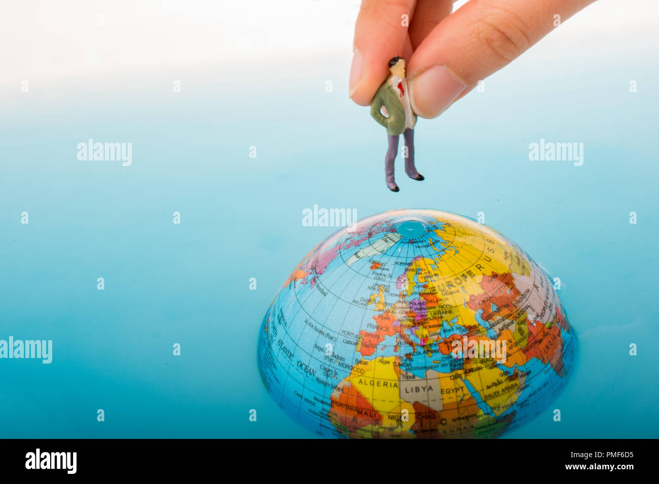 da8584622285 Hand holding a little figurine on the top of the globe in water ...