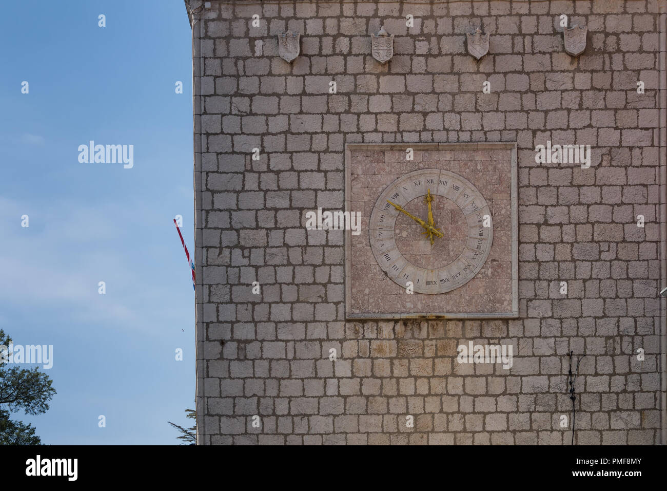 Tower made of stone tiles with clock. Clock are in a square, inner circle, roman numbers. Big square, historic part of town Krk, island Krk, Croatia. - Stock Image