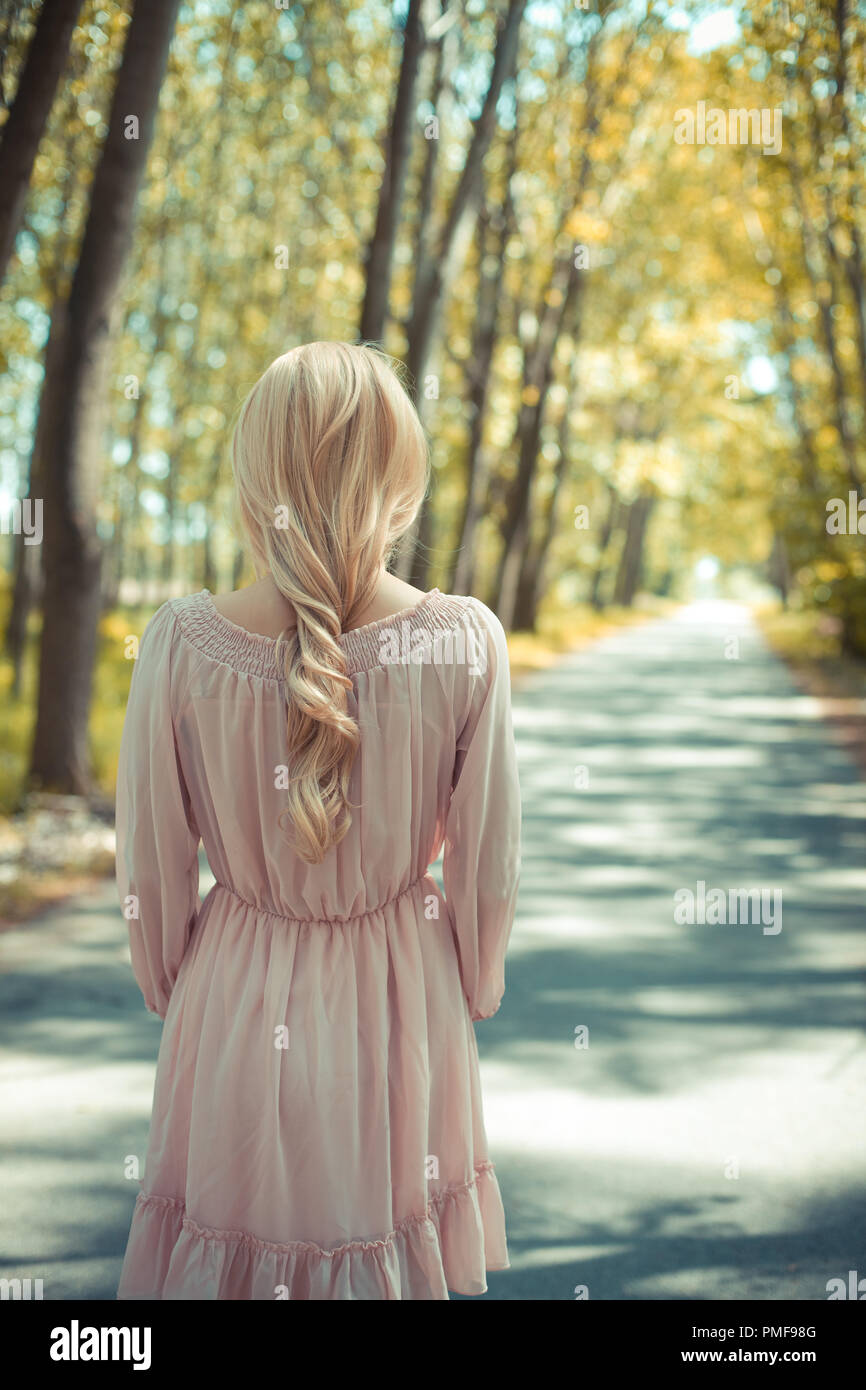 Blonde woman in pink dress standing at autumn country road - Stock Image