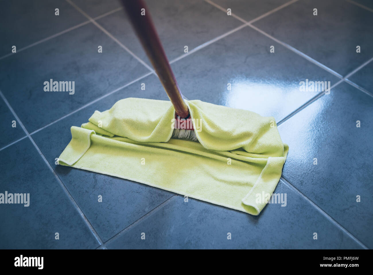 damp wiping tiled floor with floor cleaning cloth - Stock Image