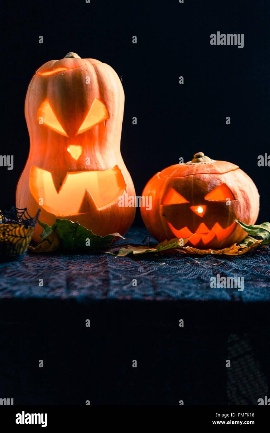 Halloween photo of two pumpkins and eyeballs on black background - Stock Image