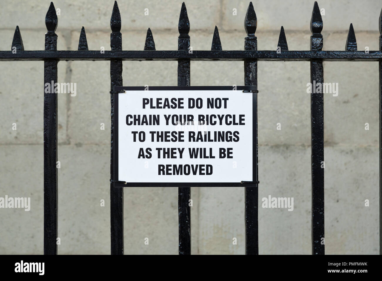 Sign showing an example of Poor grammar in Whitehall, it would read better if it stated 'Bicycles chained to these railings will be removed.' - Stock Image