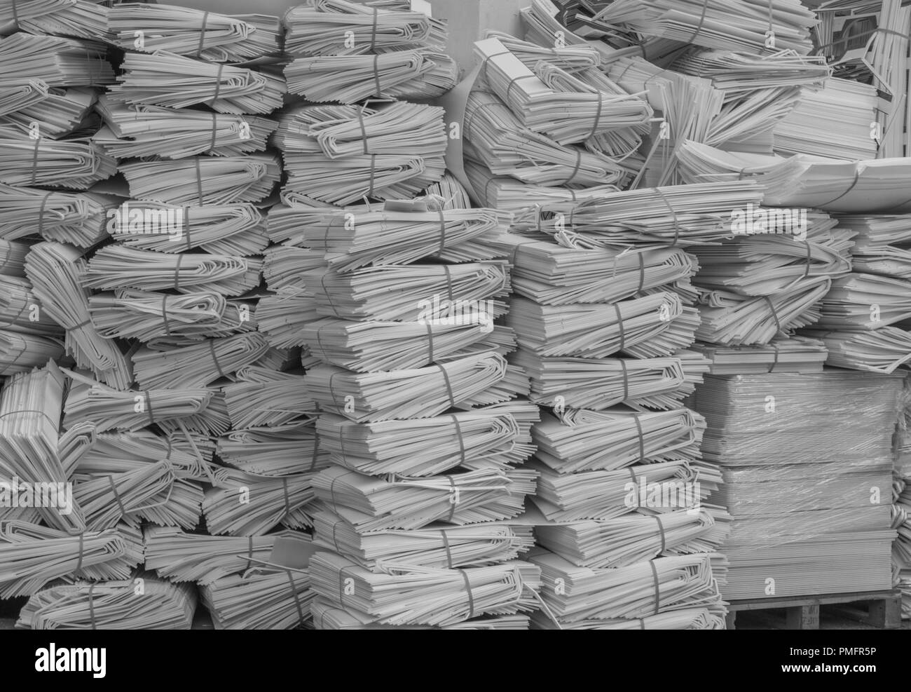 Paper Stacks in Black and White-isolated shot of paper stacks in bound bunches, for recycling, in black and white - Stock Image