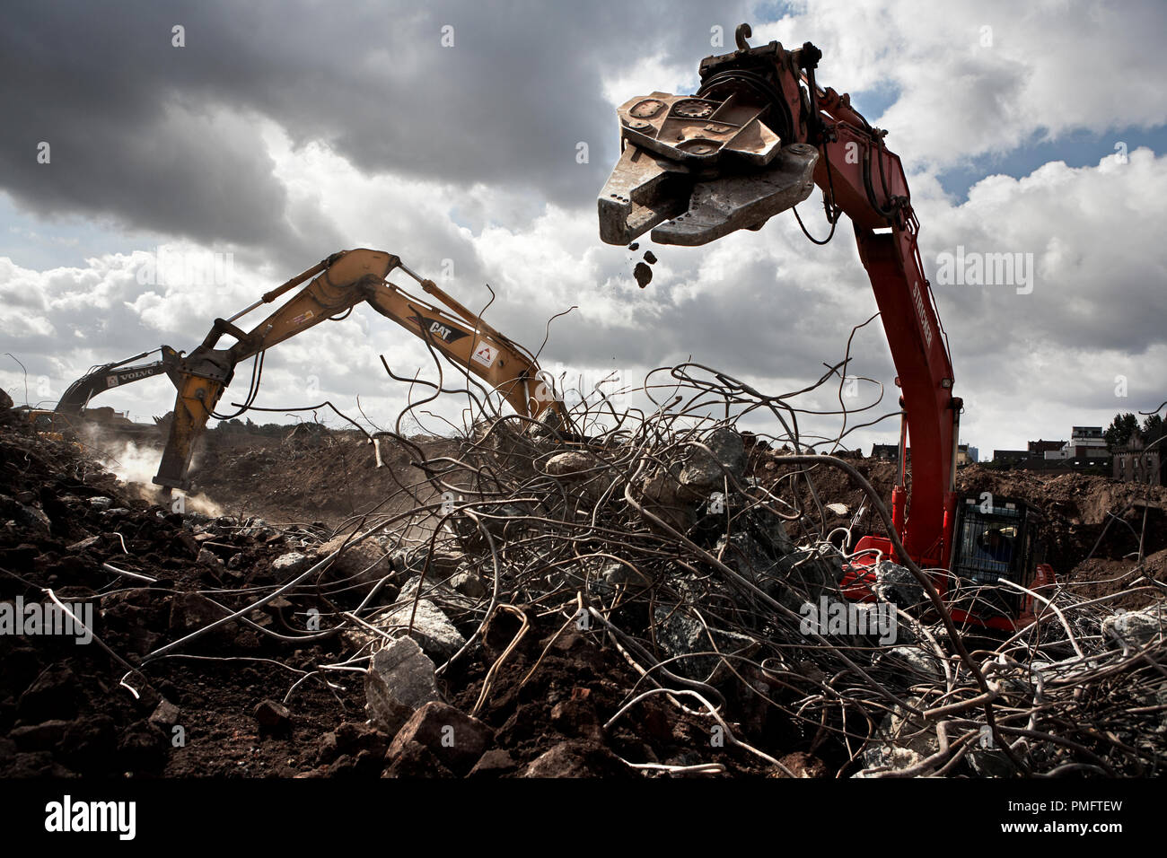Like Dinosauria, the excavators work with special grippers through huge tents made of steel wires, which were collected during the construction work on the grounds of the former Phoenixstahlwerk in Dortmund Hoerde. Where in 2003 Chinese workers dismantled a complete steel and rolling mill at record speed and rebuilt it in China. - Stock Image
