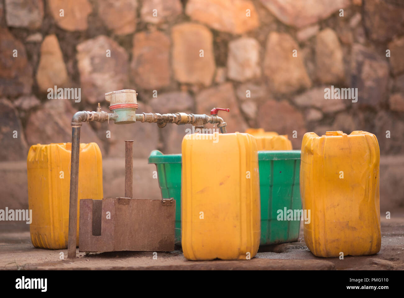 Jerrycans and buckets next to a tap to collect water in Nyamirambo, a semi-rural part of Kigali, Rwanda - Stock Image