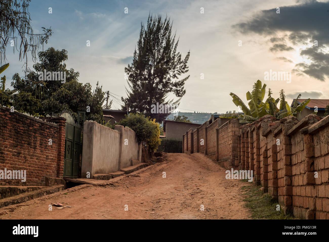 View of a dirt road between houses in Nyamirambo, an outlying suburb of Kigali, Rwanda - Stock Image