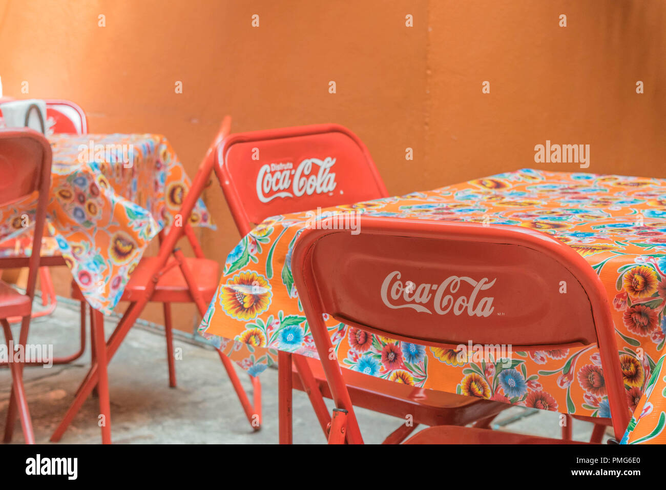 Interior restaurant with a stone floor, tables with bright flowery tablecloths, bright red metal chairs that say coca-cola and orange walls, in Mexico - Stock Image