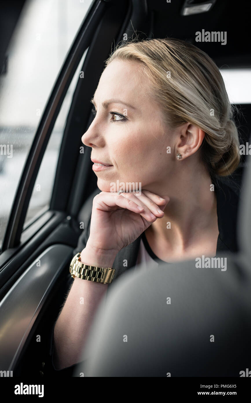 Businesswoman looking through car's window - Stock Image