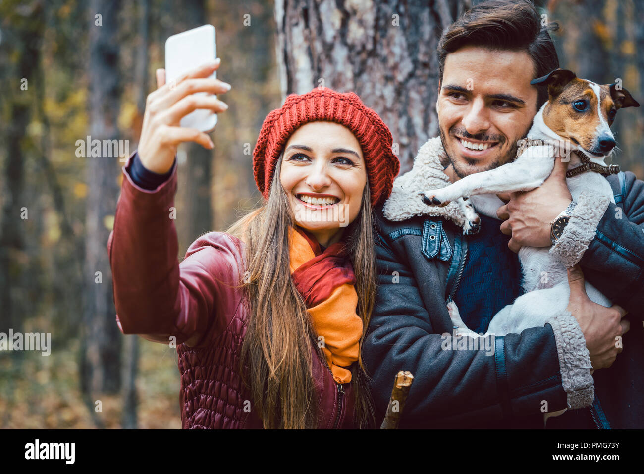Woman and man with their dog on autumn walk taking a phone selfie Stock Photo