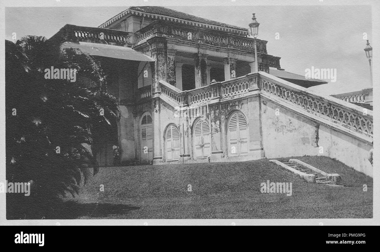 Black and white photograph on cardstock, with an image of a palatial, stone or concrete building, possibly a private home, shot from a low angle, in three-quarter view, with arched wooden doors at ground level, a grand staircase leading to the first floor, pillars supporting an open, front porch area, and an expansive rooftop verandah, likely collected as a tourist souvenir during a trip to South Asia (likely India), 1910. () - Stock Image