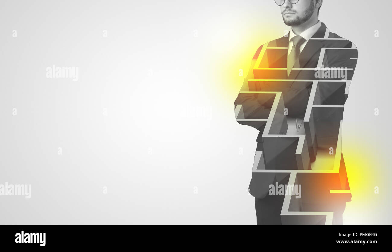 Young businessman in suit standing with maze graphic  - Stock Image