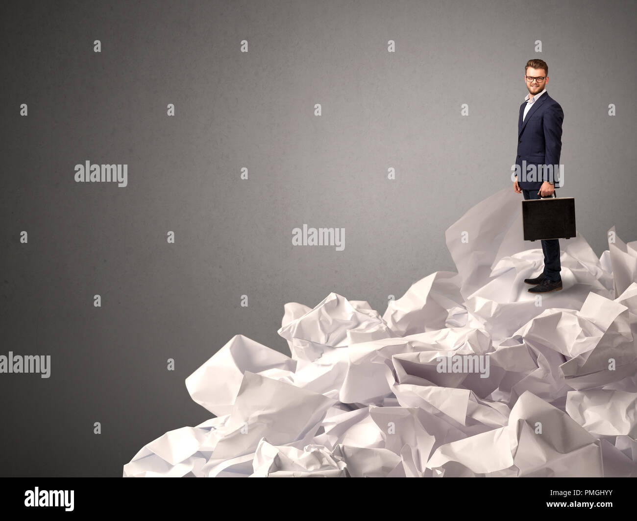 Thoughtful young businessman standing on a pile of crumpled paper with a deep grey background - Stock Image