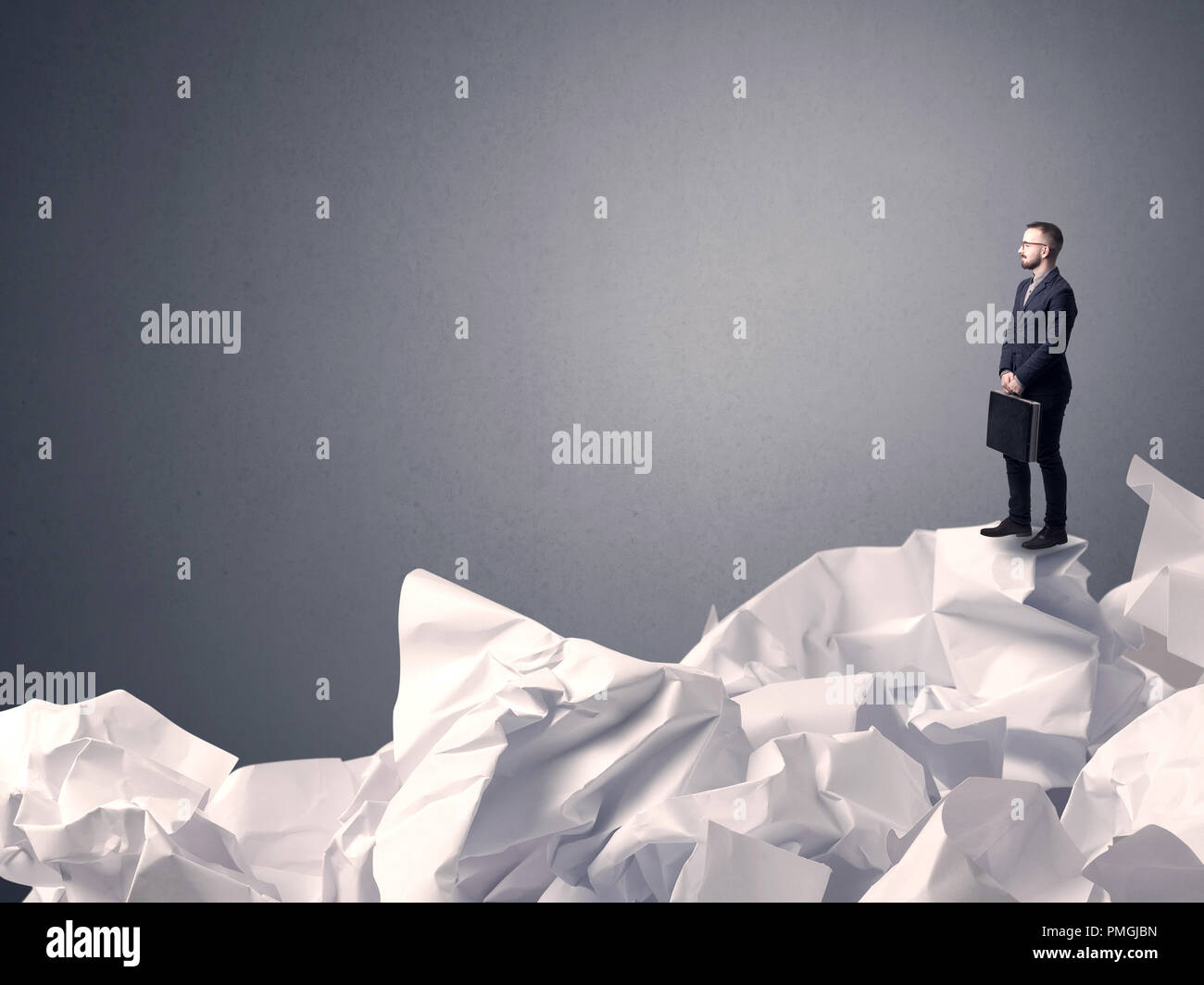 Thoughtful young businessman standing on a pile of crumpled paper with a grey background - Stock Image