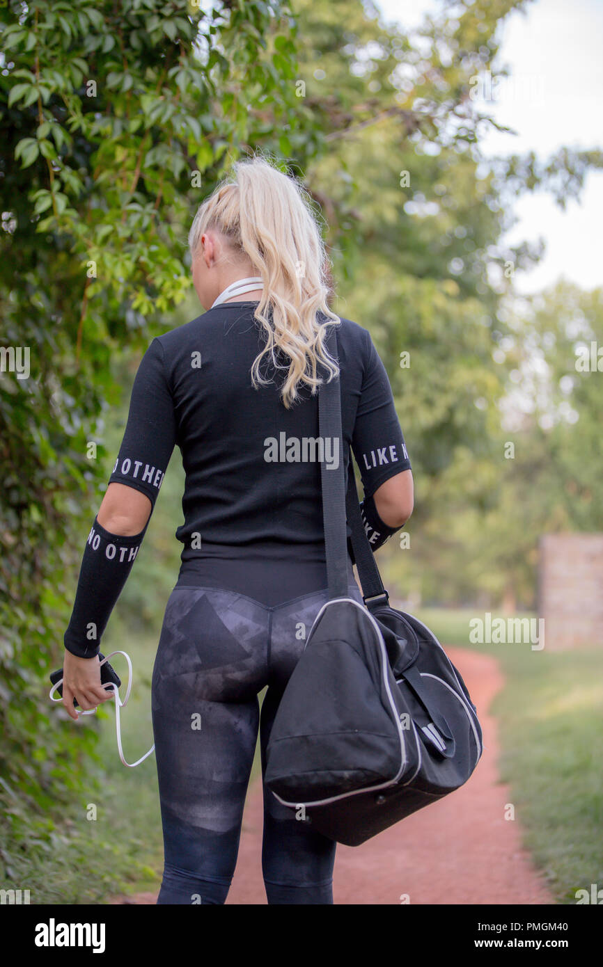 6a2b5c6e Portrait of fit young woman carrying gym bag. Fitness woman in sports  clothing going to gym