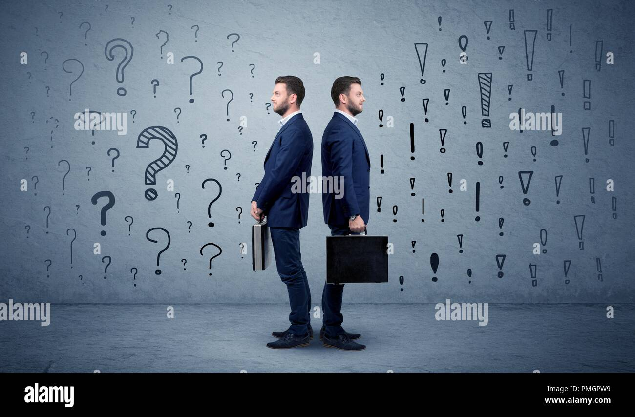 Young conflicted businessman choosing between two directions with question and exclamation marks  - Stock Image