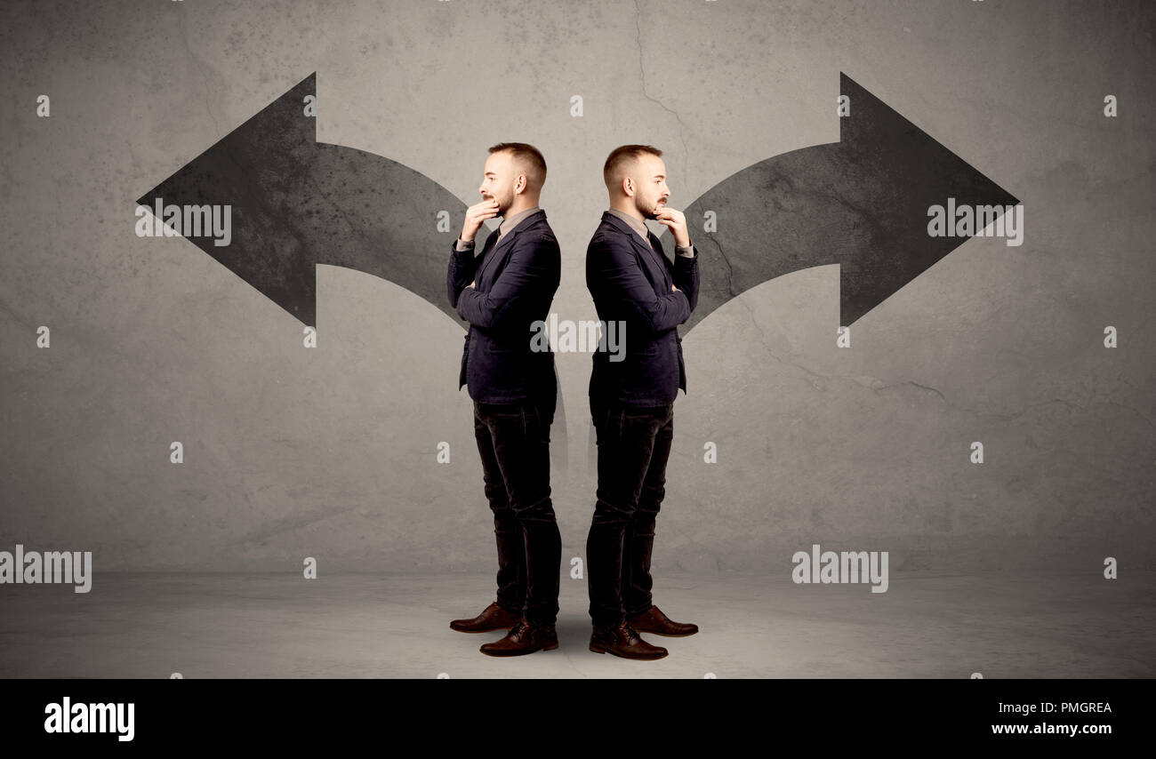 Young conflicted businessman choosing between two directions represented by black arrows - Stock Image