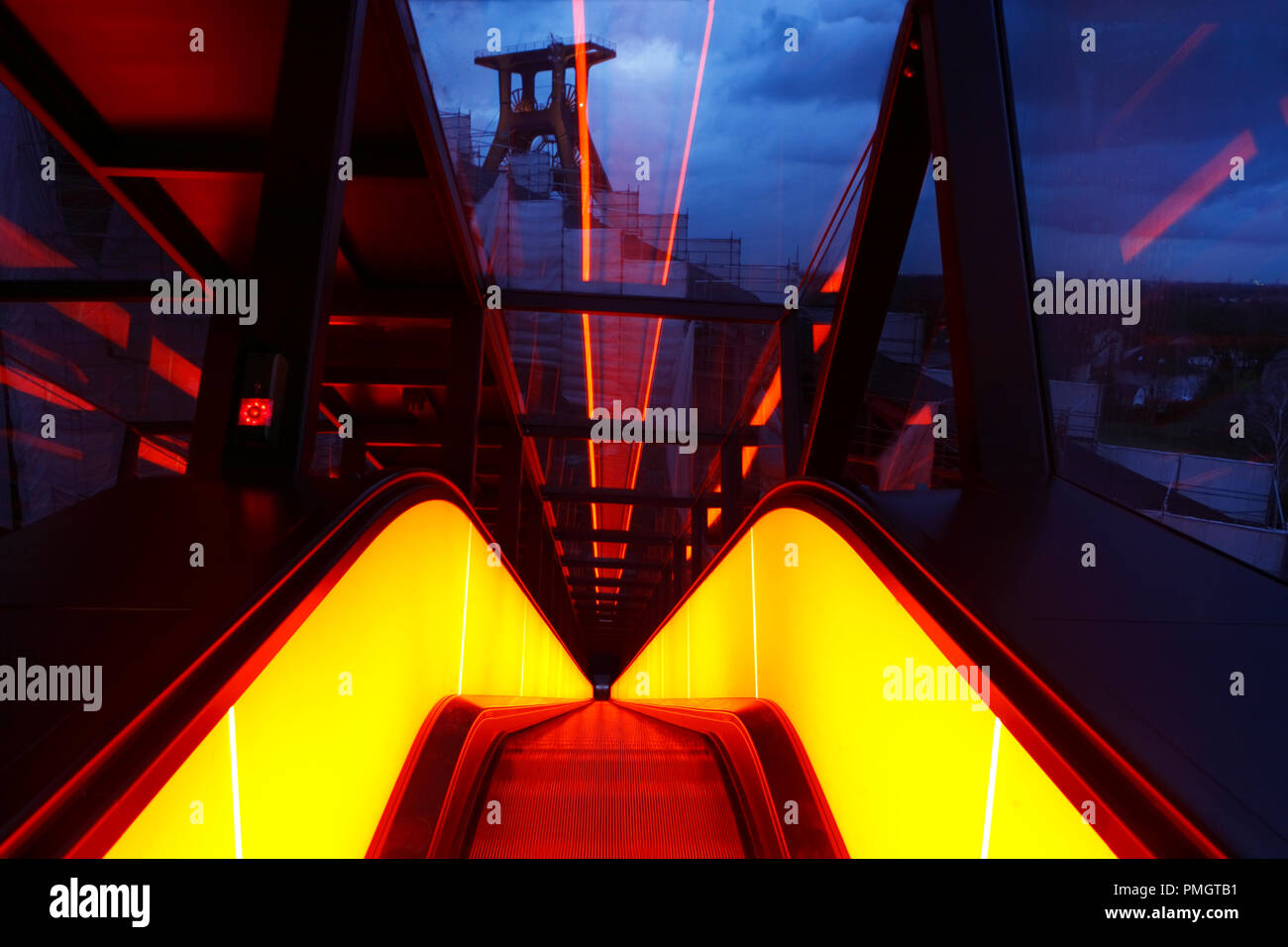 Escalator to the former coal washing on the colliery Zollverein reminds of glowing steel on a rolling street. At the beginning of twilight, the building lighting of the UNESCO World Cultural Heritage begins. - Stock Image