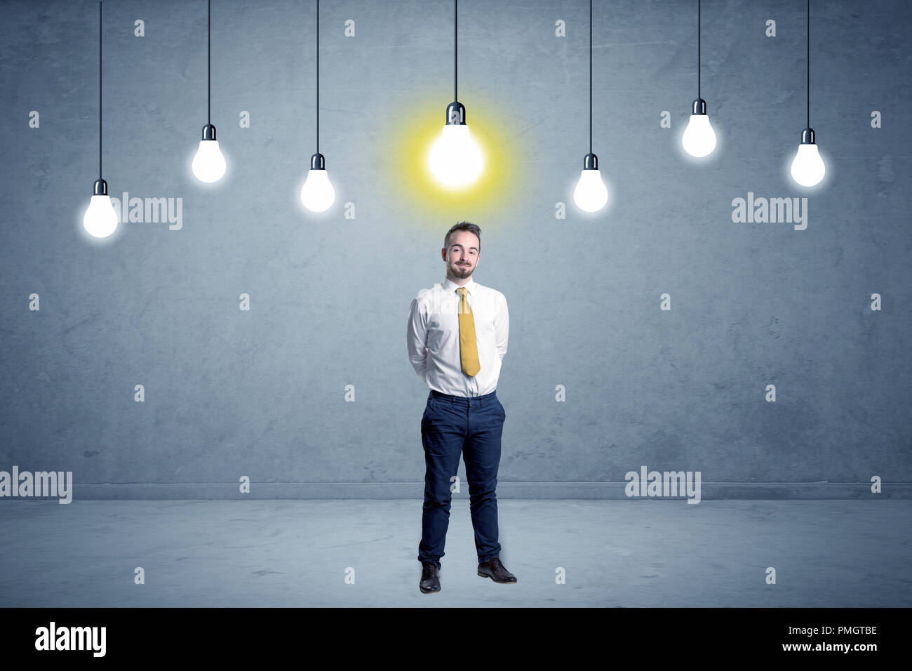 Handsome businessman in an empty space with bulbs above and uninspired face  - Stock Image