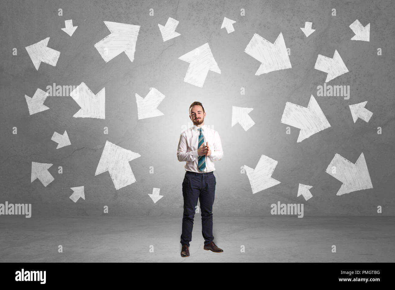 Handsome businessman standing in front of a wall with chalk drawn arrows - Stock Image