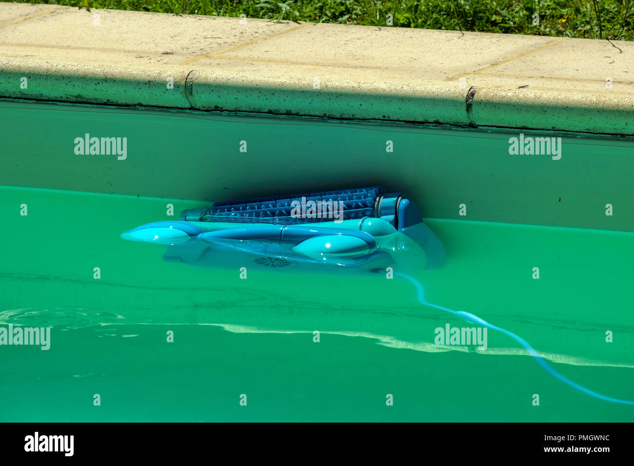 An automatic robot pool cleaner climbs the side of a cloudy ...