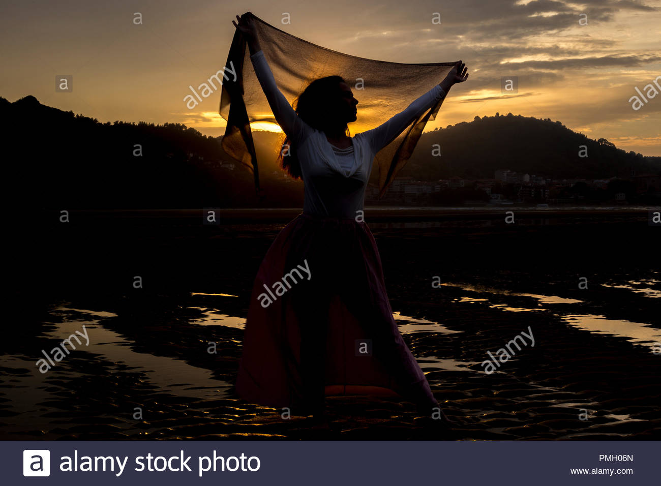 Melancholic woman while the sun goes down - Stock Image