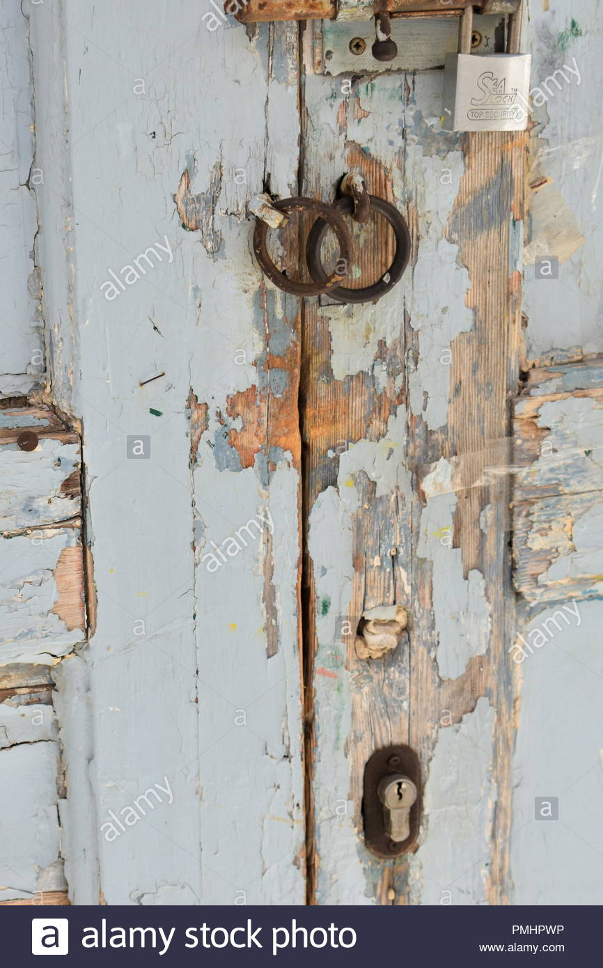 A scuffed painted old door with various locks - Stock Image