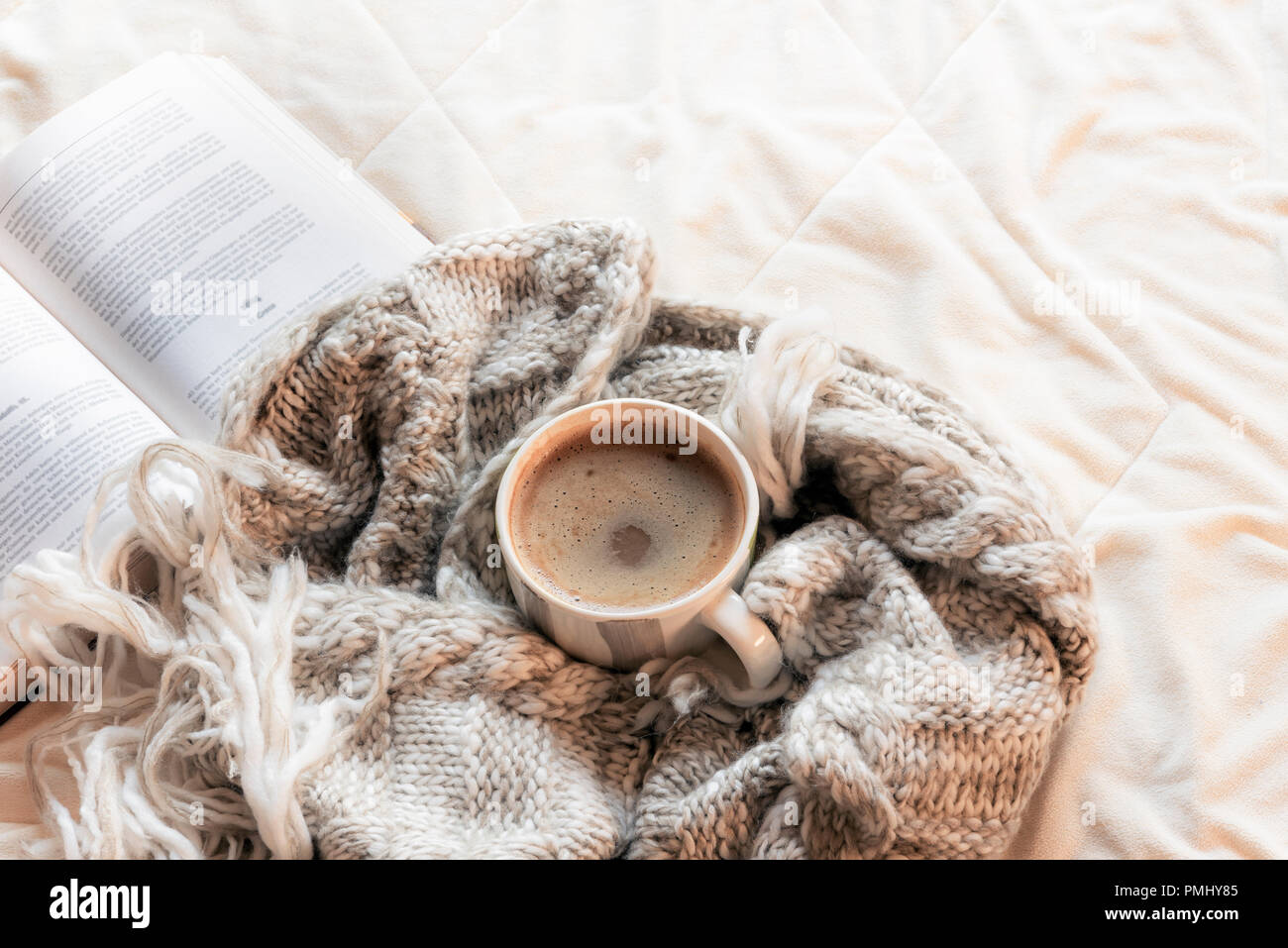 Fluffy shawl wrapped around a cup of hot chocolate, in front of an open book, on white sheets in a bright light, indoors. - Stock Image