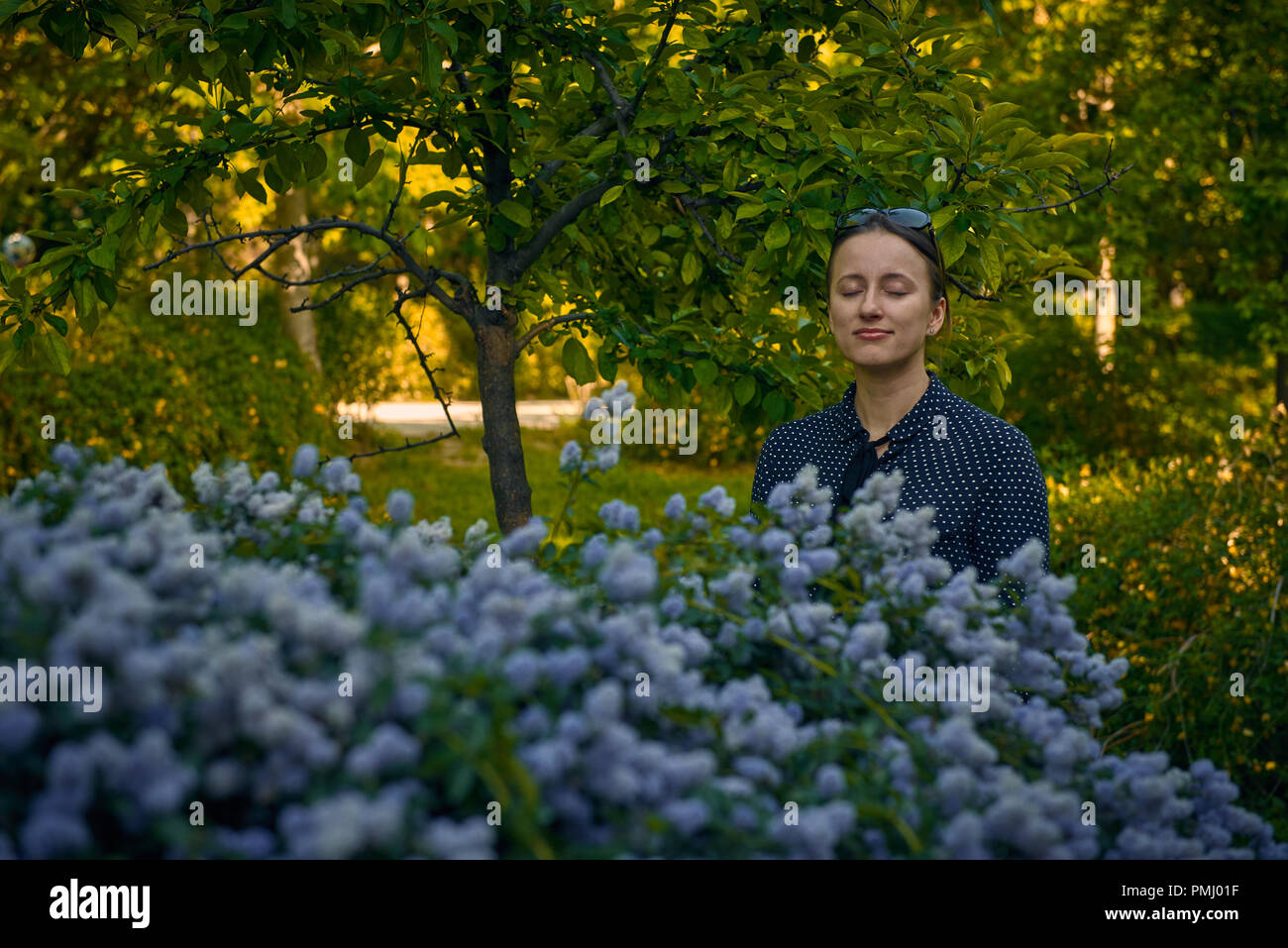 Smiling young caucasian woman with shut eyes standing near the blooming bush with blue flowers in the public park - Stock Image