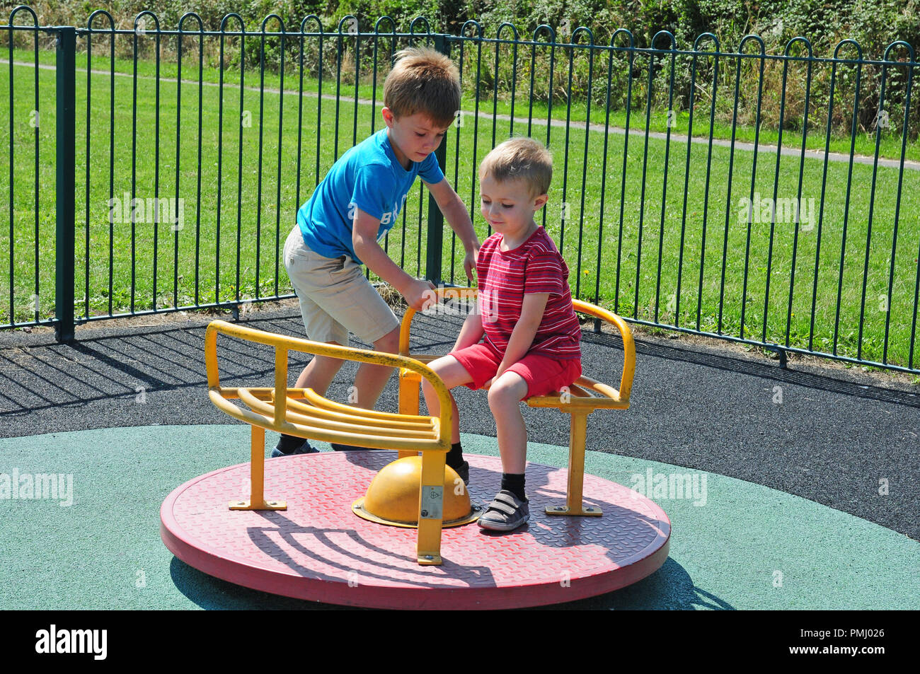 Two small boys playing on a roundabout in a play park. Stock Photo