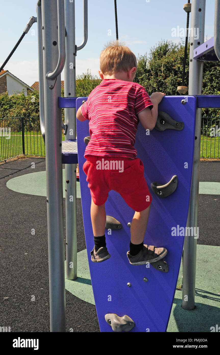 Four year old boy climbing a climbling wall up to a slide in a play park. - Stock Image