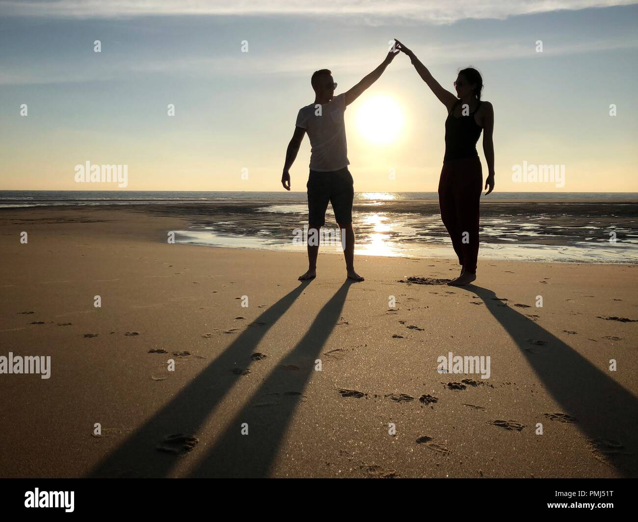 Silhouette of a Man and woman messing about on a beach, Pointe Espagnole, La Tremblade, Charente-Maritime, France - Stock Image