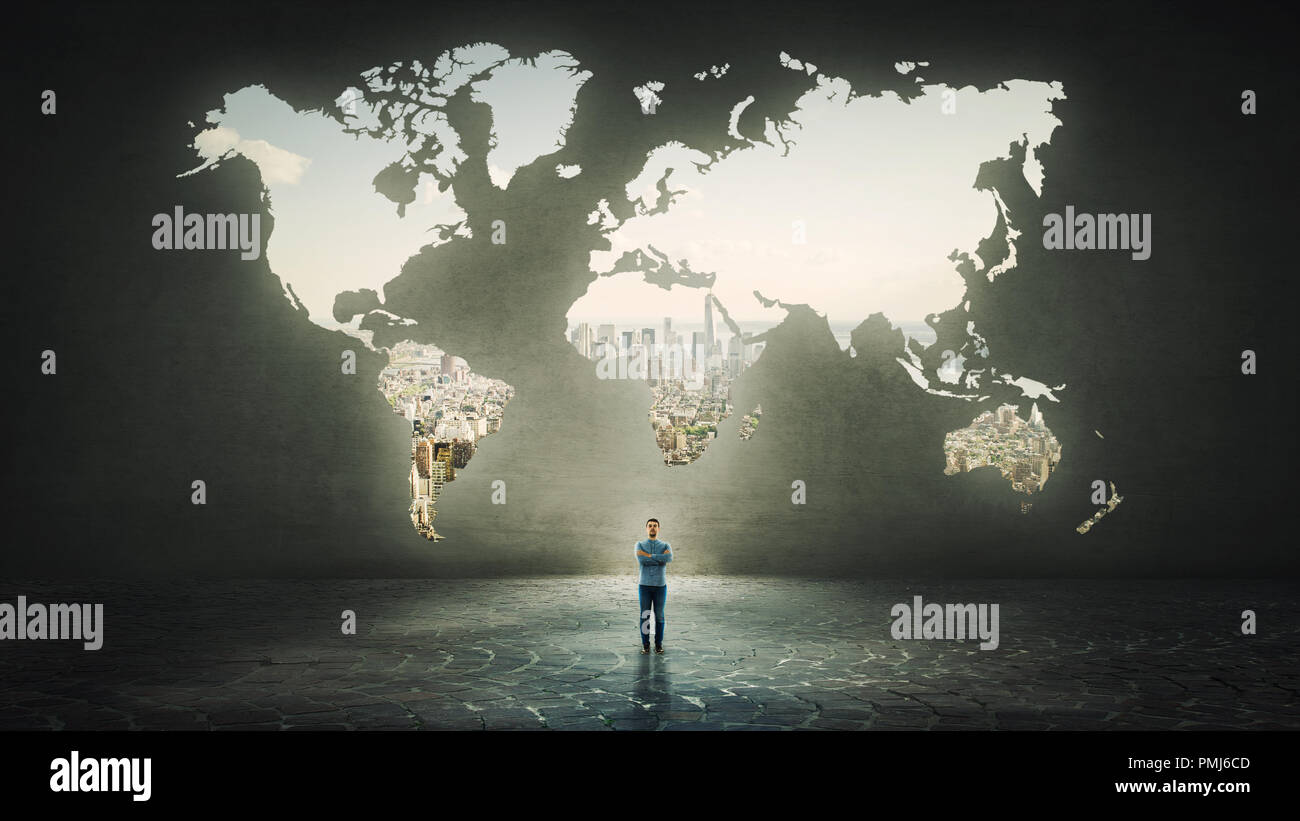 Confident businessman with crossed hands standing alone in front of the world map hole as a window shaped in a concrete wall with a view to the city. - Stock Image