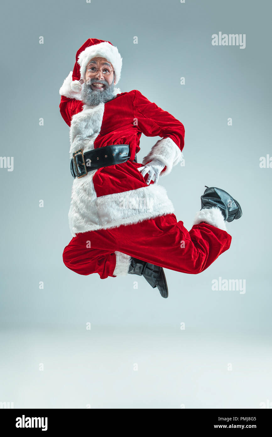Funny serious guy with christmas hat dancing at studio. New Year ...