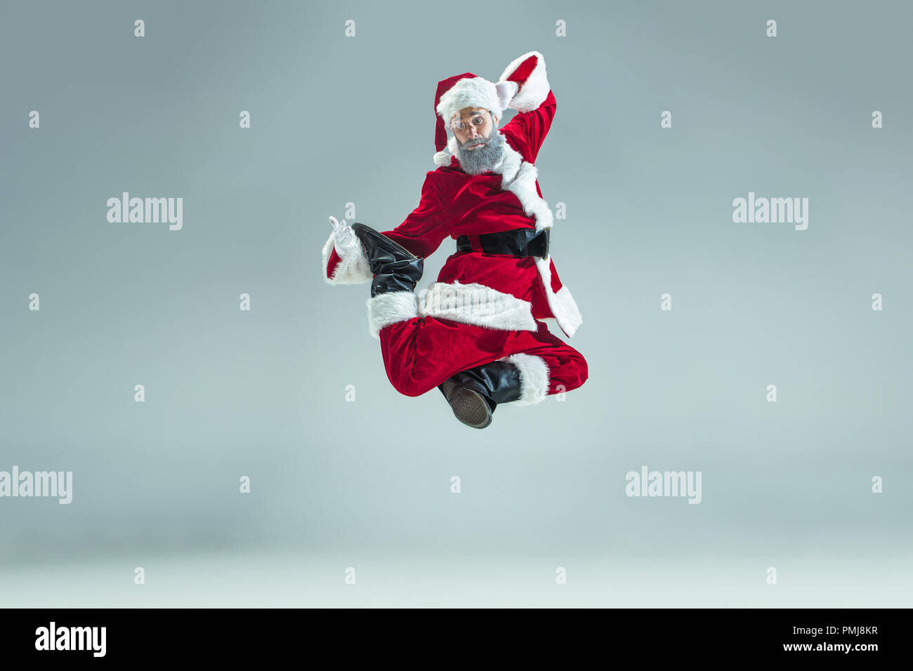 98bf99b2269 ... arriving 6f35f c6b1c Funny serious guy with christmas hat dancing at  studio.