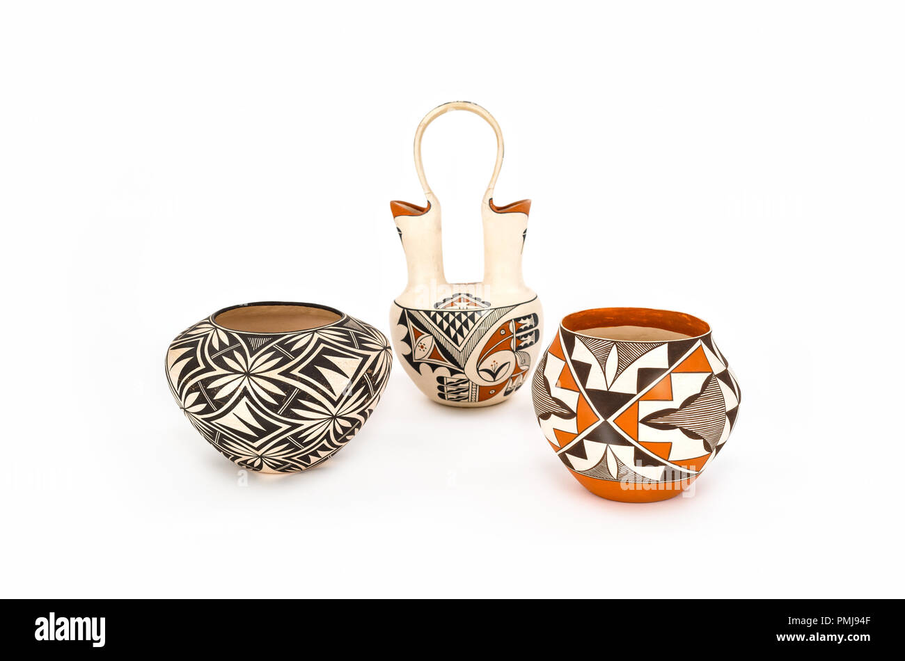 Three pieces of authentic Native American Pottery with a white background. Bright colors and intricate patterns. - Stock Image