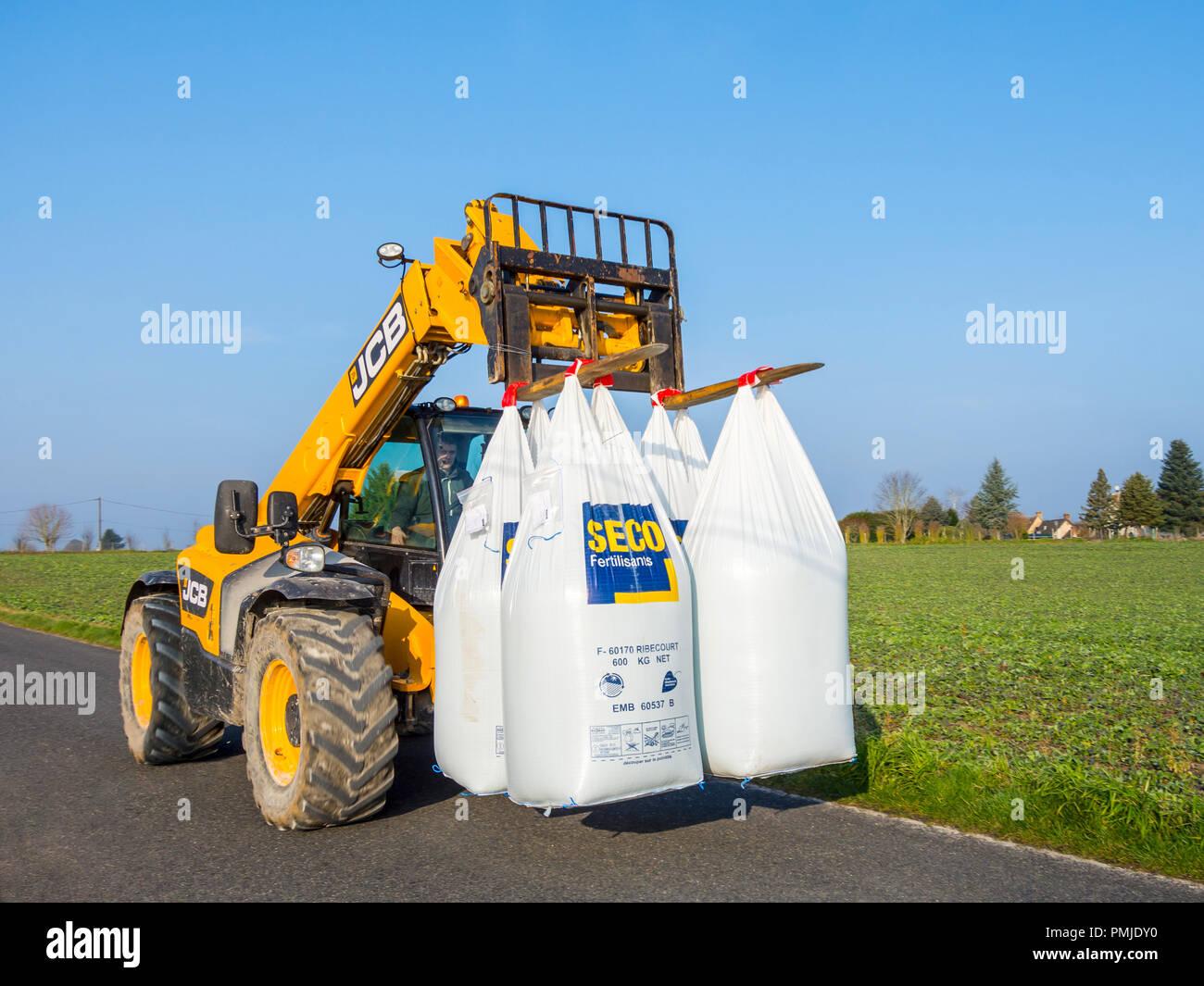 JCB Telescopic tractor carrying large sacks of fertiliser - France. - Stock Image